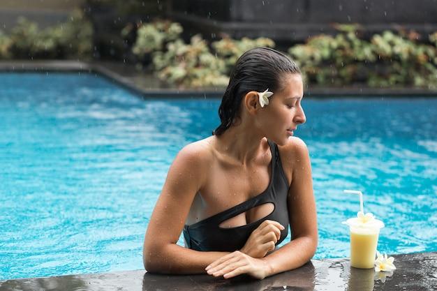 Kobieta w basenie z napojem owocowym.