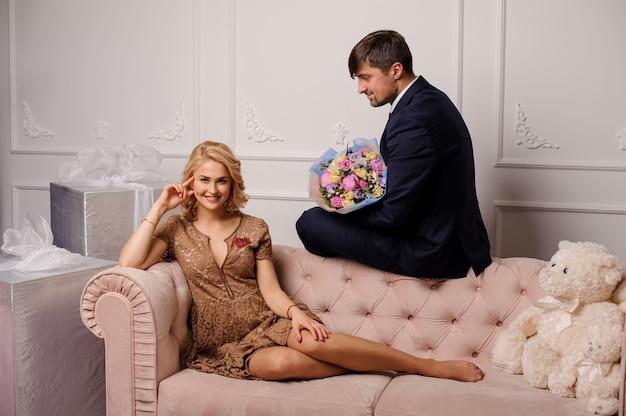 Kobieta w beżowej sukience leżąca na kanapie i mężczyzna siedzący na niej z bukietem