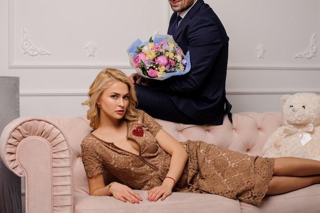 Kobieta w beżowej sukience leżąca na kanapie i mężczyzna siedzący na niej