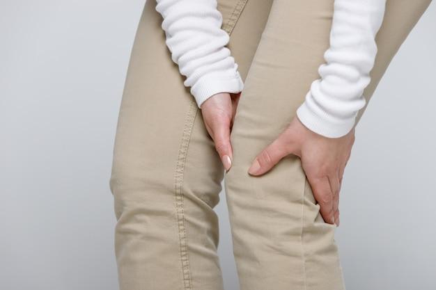 Kobieta w beżowych spodniach cierpiących na ból kolana lub choroby zwyrodnieniowej stawów, na białym tle