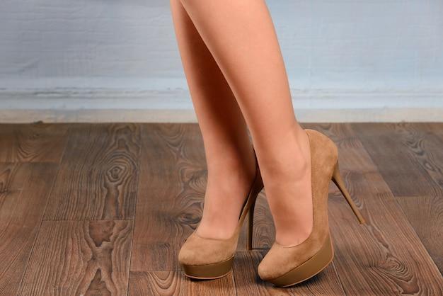 Kobieta w beżowych zamszowych butach na obcasie na drewnianej podłodze