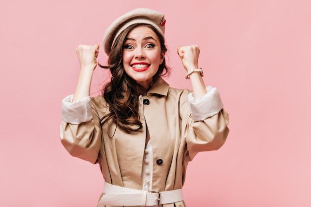 Kobieta w beżowym płaszczu cieszy się szczęściem i patrzy na aparat z uśmiechem na różowym tle.