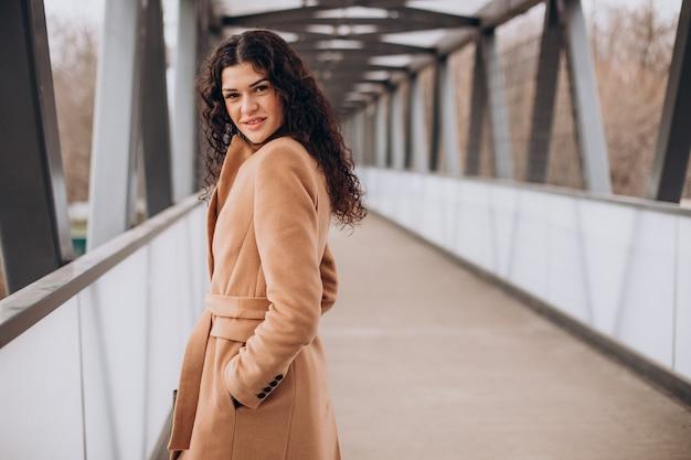 Kobieta w beżowym płaszczu spacerująca po mieście