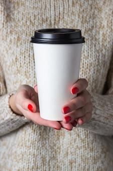 Kobieta w beżowym swetrze trzyma papierową filiżankę kawy