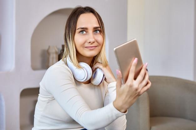 Kobieta w bezprzewodowych słuchawkach robi selfie w pomieszczeniu