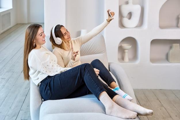 Kobieta w bezprzewodowych słuchawkach robi selfie z siostrą przez telefon w pomieszczeniu