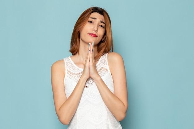Kobieta w białej bluzce i niebieskich dżinsach, modląc się i prosząc