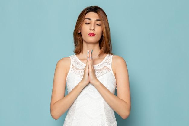 Kobieta w białej bluzce i niebieskich dżinsach modląc się poza
