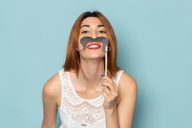 Kobieta w białej bluzce i niebieskich dżinsach próbuje fałszywych wąsów