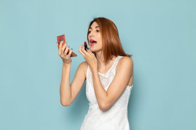 Kobieta w białej bluzce i niebieskich dżinsach robi makijaż