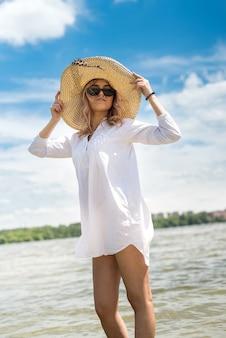 Kobieta w białej bluzce i słomkowym kapeluszu odpoczywa w gorący letni dzień chodząc po jeziorze