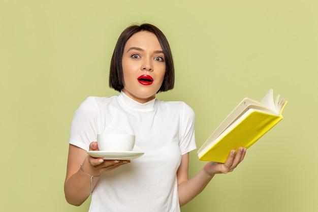Kobieta w białej bluzce i zielonej spódnicy czytając książkę przy filiżance herbaty