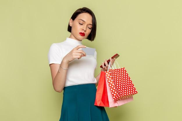 Kobieta w białej bluzce i zielonej spódnicy trzyma pakiety zakupów i telefon modelka odzieży damskiej