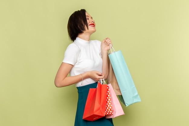 Kobieta w białej bluzce i zielonej spódnicy trzyma pakiety zakupów z uśmiechem i stanowią modelka kobiecych ubrań