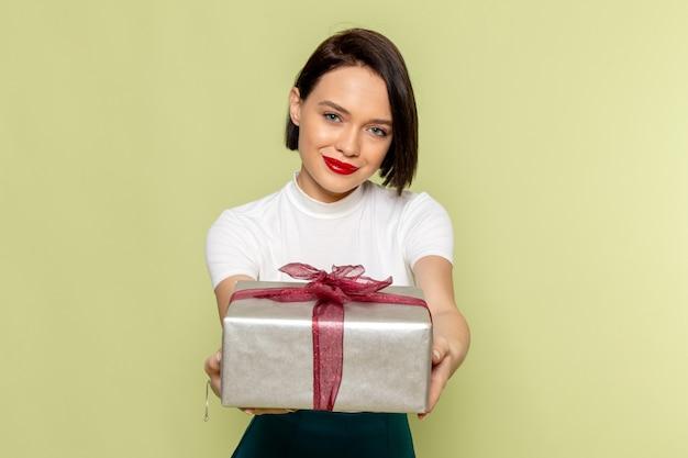 Kobieta w białej bluzce i zielonej spódnicy, trzymając obecne pudełko