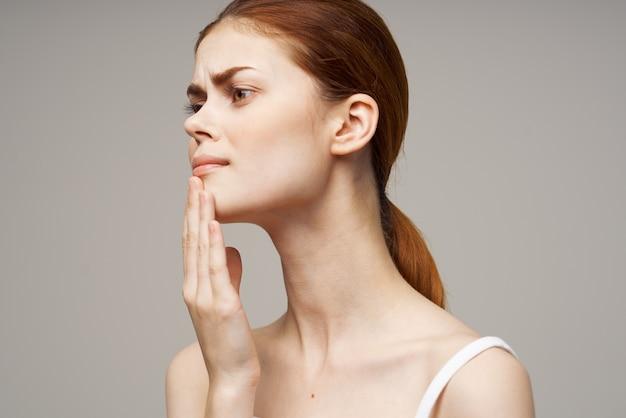 Kobieta w białej koszulce ból zęba problemy zdrowotne zaburzenie jasne tło