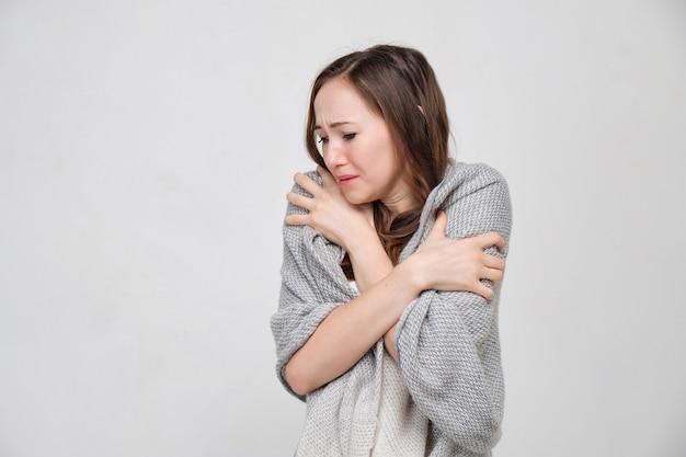 Kobieta w białej koszulce była pokryta ciepłym płaszczem, aby był ciepły od zimna.
