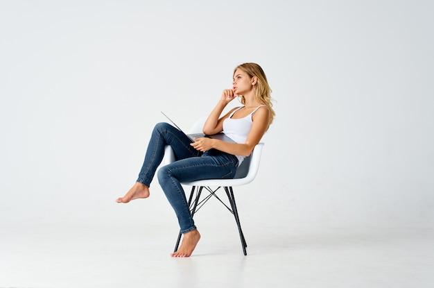 Kobieta w białej koszulce i dżinsach siedzi na krześle pozowanie jasne tło