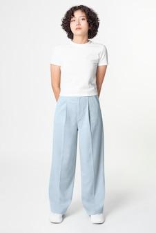 Kobieta w białej koszulce i niebieskich luźnych spodniach minimalistyczna moda