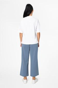 Kobieta w białej koszulce i niebieskich luźnych spodniach minimalna moda widok z tyłu
