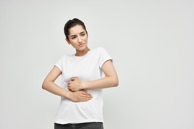Kobieta w białej koszulce leczenie bólu brzucha z powodu dyskomfortu