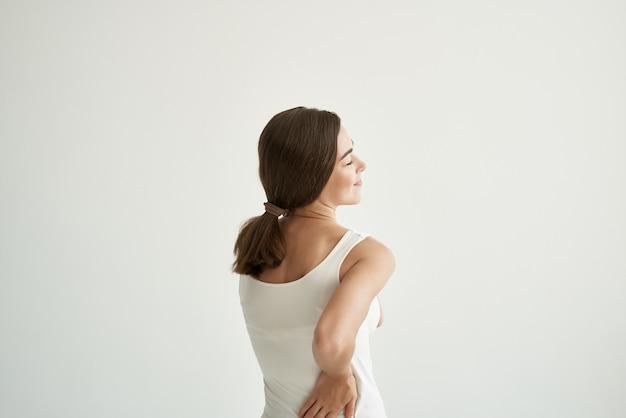 Kobieta w białej koszulce leczenie bólu stawów zdrowie światło tło