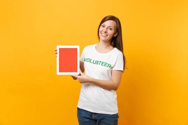 Kobieta w białej koszulce napisany napis zielony tytuł wolontariusz trzymać komputer typu tablet pc, pusty pusty ekran na białym tle na żółtym tle. dobrowolna bezpłatna pomoc pomoc, koncepcja pracy łaski charytatywnej.