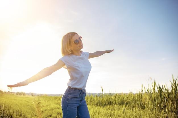 Kobieta w białej koszulce, okularach przeciwsłonecznych i dżinsach rozłożyła ręce