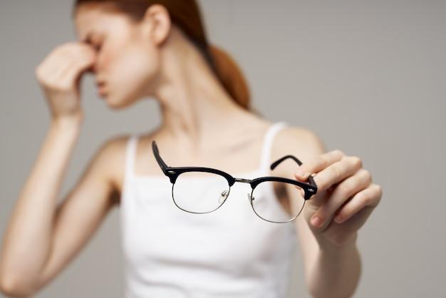 Kobieta w białej koszulce okulary problemy ze wzrokiem krótkowzroczność