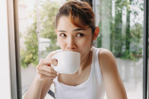 Kobieta w białej koszulce pije gorący napój w filiżance