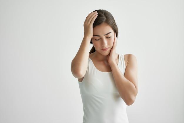 Kobieta w białej koszulce problem zdrowotny ból głowy emocje niezadowolenie
