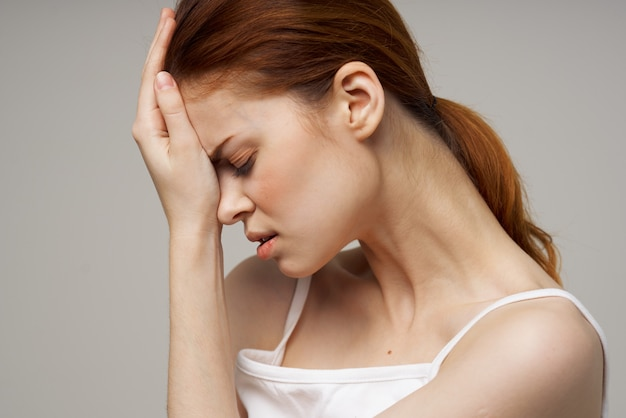 Kobieta w białej koszulce trzyma na białym tle zaburzenia migreny głowy