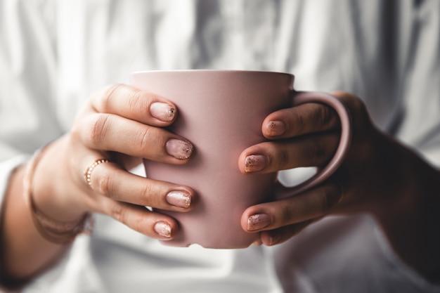 Kobieta w białej koszulce trzyma poranną kawę w różowym ceramicznym kubku. manicure. przedni widok