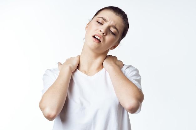 Kobieta w białej koszulce trzymająca się za ramiona ból szyi problemy zdrowotne dyskomfort