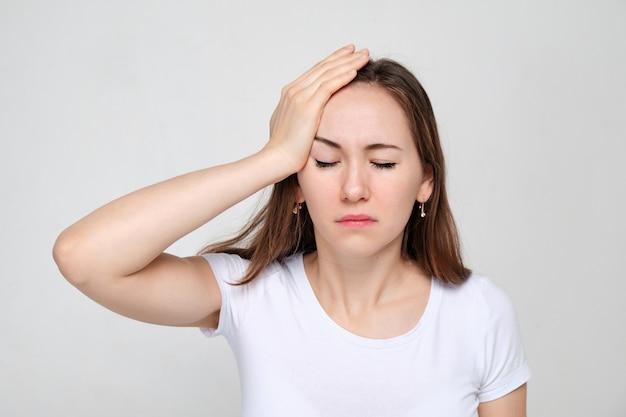 Kobieta w białej koszulce trzymającej rękę za głowę cierpi na zapomnienie. problemy z pamięcią
