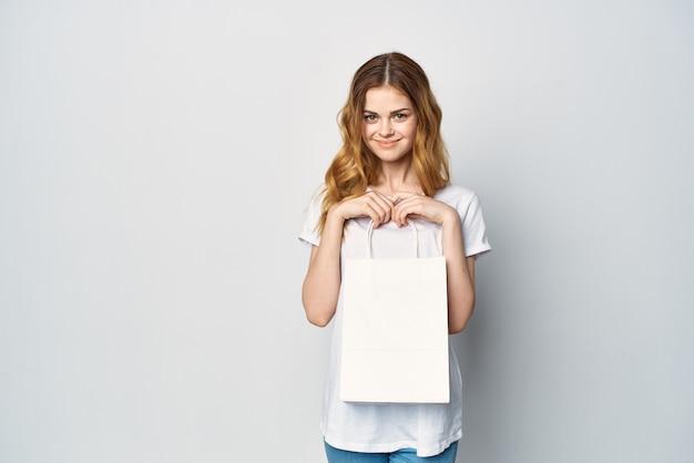 Kobieta w białej koszulce z białym opakowaniem w rękach zakupy rozrywka spacer