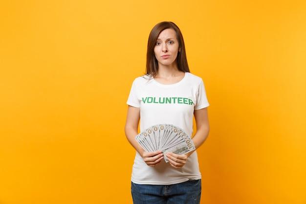 Kobieta w białej koszulce z napisem zielony tytuł wolontariusz trzymać wiele banknotów dolarów, pieniądze w gotówce na białym tle na żółtym tle. dobrowolna bezpłatna pomoc pomoc, koncepcja pracy łaski charytatywnej.