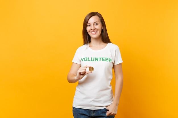 Kobieta w białej koszulce z napisem zielony tytuł wolontariusz trzymaj bitcoin, waluta przyszłości metalowej monety na białym tle na żółtym tle. dobrowolna bezpłatna pomoc, koncepcja pracy charytatywnej