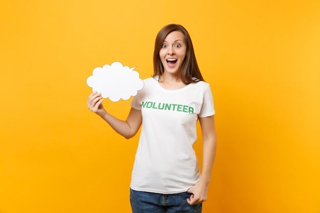 Kobieta w białej koszulce z napisem zielony tytuł wolontariusza przytrzymaj puste puste say chmura dymek na białym tle na żółtym tle. dobrowolna bezpłatna pomoc pomaga koncepcja pracy łaski charytatywnej.