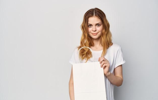 Kobieta w białej koszulce z paczkami w rękach zakupy rozrywka lifestyle