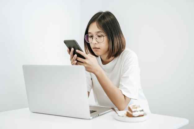 Kobieta w białej koszuli, grająca w smartfona i posiadająca laptopa.