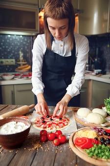 Kobieta w białej koszuli i fartuchu, stawiając składniki na pizzę
