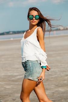 Kobieta w białej koszuli i stylowe okulary przeciwsłoneczne, pozowanie na plaży.