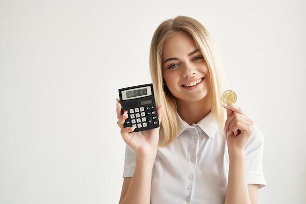 Kobieta w białej koszuli kalkulator złota moneta kryptowaluta