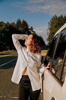 Kobieta w białej koszuli obok białego samochodu na drodze