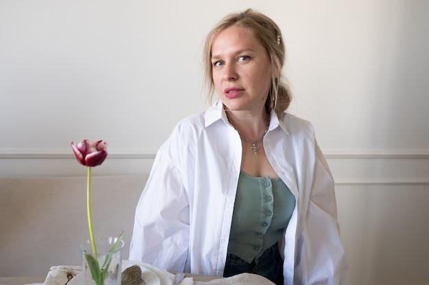Kobieta w białej koszuli przy stole.