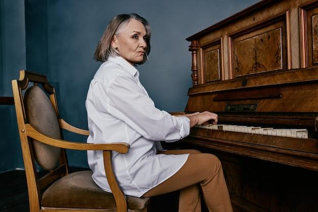 Kobieta w białej koszuli siedzi na krześle obok fortepianu ucząc się muzyki