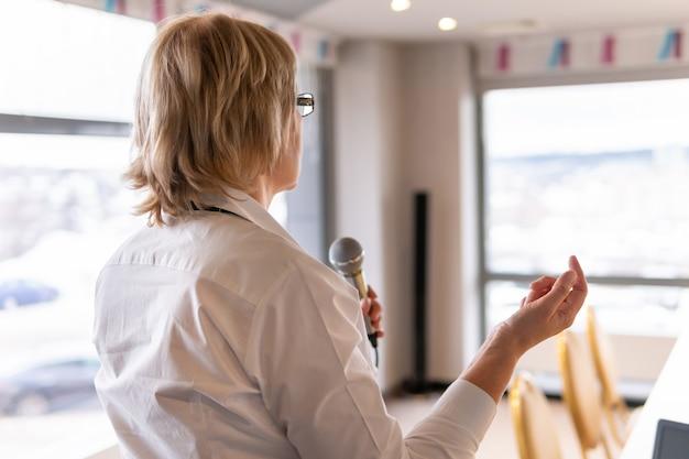 Kobieta w białej koszuli trenuje słuchaczy w pokoju biznesowym