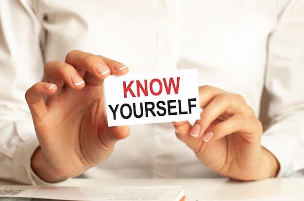Kobieta w białej koszuli trzyma kartkę z napisem: poznaj siebie.