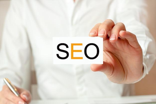 Kobieta w białej koszuli trzyma kartkę z napisem: seo. koncepcja biznesowa dla firm. seo - skrót od search engine optimization.